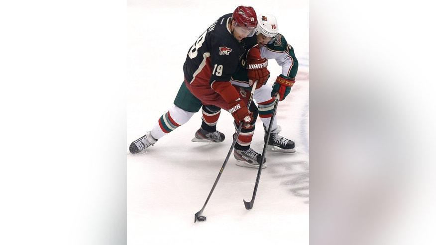 Minnesota Wild Devin Setoguchi (10) and Phoenix Coyotes' Shane Doan (19) battle for the puck during the first period of an NHL hockey game, Monday, Feb. 4, 2013, in Glendale, Ariz. (AP Photo/Matt York)