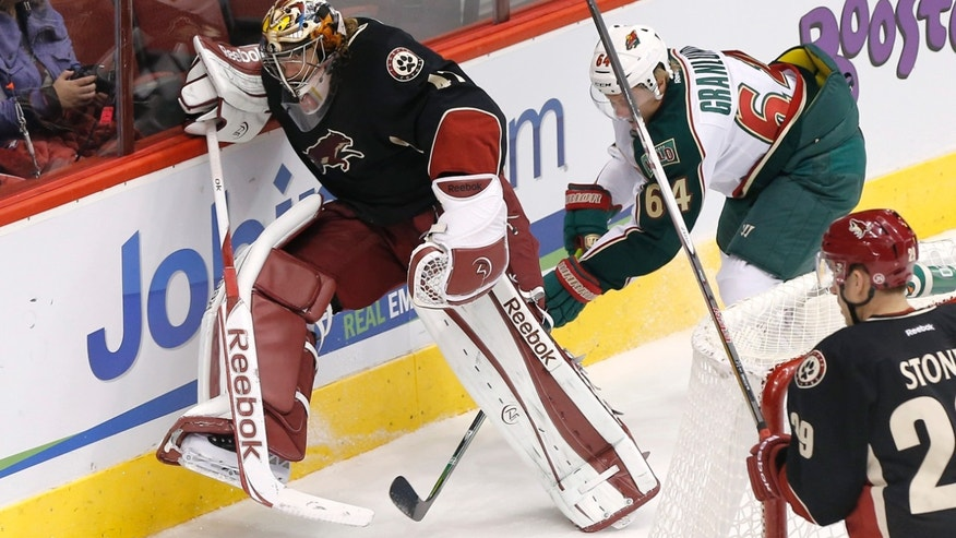 Phoenix Coyotes goalie Mike Smith, left, kicks the puck away from Minnesota Wild Mikael Granlund (64), of Finland, during the first period of an NHL hockey game, Monday, Feb. 4, 2013, in Glendale, Ariz. (AP Photo/Matt York)