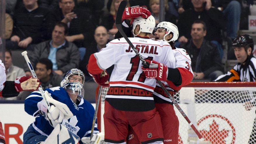 Carolina Hurricanes center Jordan Staal celebrates with teammate Patrick Dwyer (39) after scoring on Toronto Maple Leafs goaltender James Reimer, left, during the second period of an NHL hockey game Monday, Feb. 4, 2013, in Toronto. (AP Photo/The Canadian Press, Frank Gunn)
