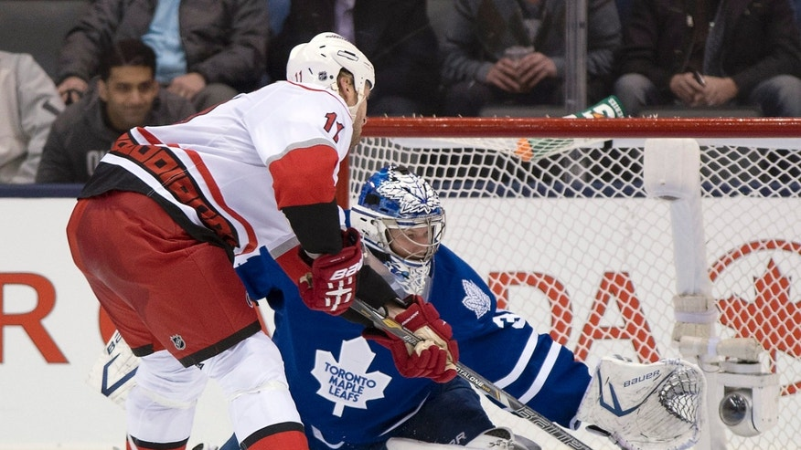 Carolina Hurricanes center Jordan Staal scores on Toronto Maple Leafs goaltender James Reimer during the second period of an NHL hockey game Monday, Feb. 4, 2013, in Toronto. (AP Photo/The Canadian Press, Frank Gunn)