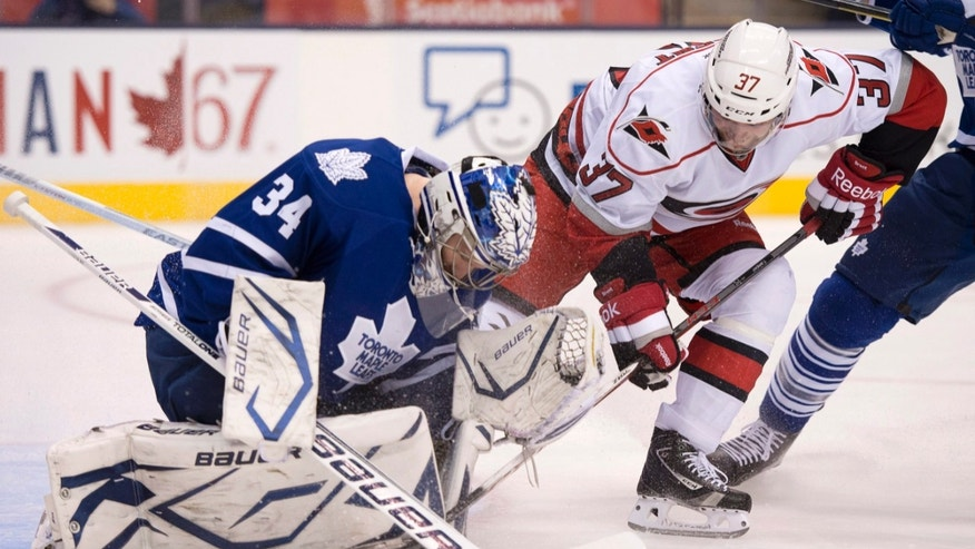 Carolina Hurricanes' Tim Brent is blocked by Toronto Maple Leafs' James Reimer during the first period of an NHL hockey game in Toronto on Monday, Feb. 4, 2013. (AP Photo/The Canadian Press, Frank Gunn)