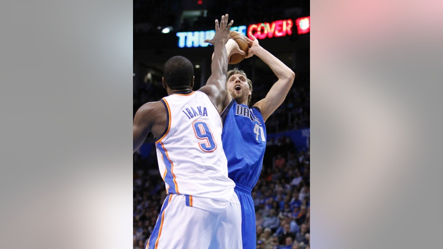 Dallas Mavericks forward Dirk Nowitzki (41) shoots in front of Oklahoma City Thunder forward Serge Ibaka (9) during the first quarter of an NBA basketball game in Oklahoma City, Monday, Feb. 4, 2013.  (AP Photo/Alonzo Adams)