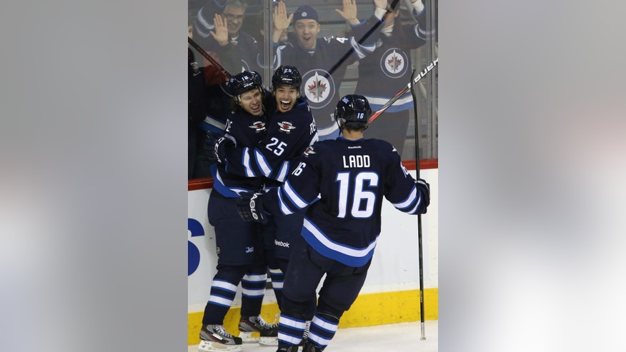 Winnipeg Jets' Bryan Little (18), Zach Redmond (25) and Andrew Ladd (16) celebrate after Little scored the game-winning goal against the Florida Panthers during overtime of an NHL hockey game in Winnipeg, Manitoba, Tuesday, Feb. 5, 2013. (AP Photo/The Canadian Press, Trevor Hagan)