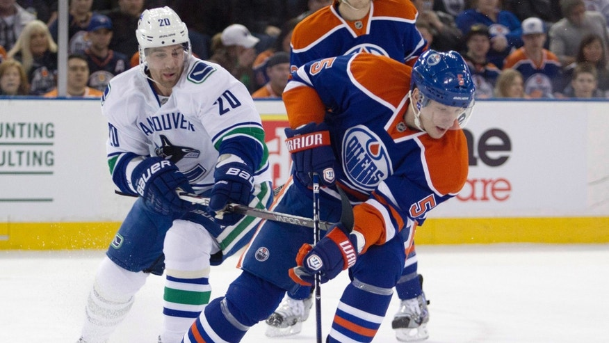 Vancouver Canucks' Chris Higgins chases Edmonton Oilers' Ladislav Smid during the first period of an NHL hockey game Monday, Feb. 4, 2013, in Edmonton, Alberta. (AP Photo/The Canadian Press, Jason Franson)