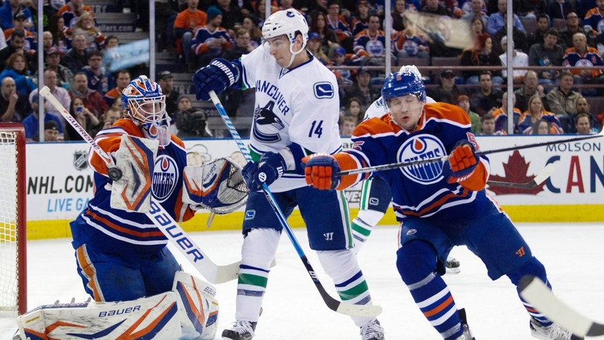 Vancouver Canucks Alexandre Burrows looks for the rebound as Edmonton Oilers goalie Devan Dubnyk makes the save during the first period of an NHL hockey game Monday, Feb. 4, 2013, in Edmonton, Alberta. At right is Oilers Ladislav Smid. (AP Photo/The Canadian Press, Jason Franson)