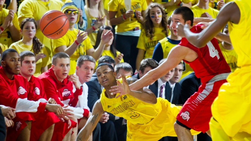 Michigan guard Trey Burke (3) saves the ball from going out of bounds as Ohio State's Aaron Craft (4) watches during the first half of an NCAA college basketball game, Tuesday, Feb. 5, 2013, at Crisler Center in Ann Arbor, Mich. (AP Photo/Tony Ding)