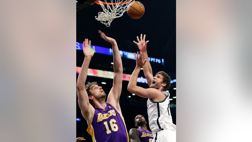 Brooklyn Nets' Brook Lopez, right, shoots over Los Angeles Lakers' Pau Gasol during the first half of the NBA basketball game at the Barclays Center Tuesday, Feb. 5, 2013 in New York.  (AP Photo/Seth Wenig)