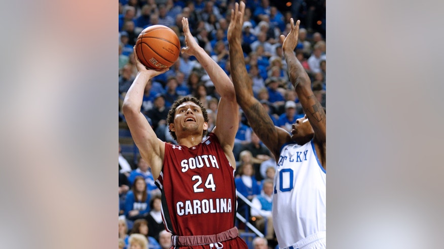 South Carolina's Michael Carrera (24) puts up a shot under pressure from Kentucky's Archie Goodwin (10) during the first half of an NCAA college basketball game at Rupp Arena in Lexington, Ky., Tuesday, Feb. 5, 2013. (AP Photo/James Crisp)