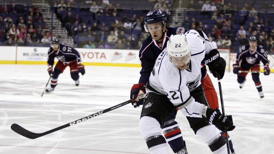 Los Angeles Kings' Trevor Lewis (22) prepares to shoot as Columbus Blue Jackets' Cody Goloubef (48) trails during the first period of an NHL hockey game Tuesday, Feb. 5, 2013, in Columbus, Ohio. (AP Photo/ Mike Munden)