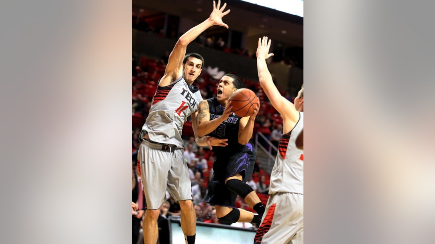 Kansas State's Angel Rodriguez drives between Texas Tech's Dejan Kravic(11) and Clark Lammert, right, during an NCAA college basketball game in Lubbock, Texas, Tuesday, Feb. 5, 2013. (AP Photo/Lubbock Avalanche-Journal, Zach Long)