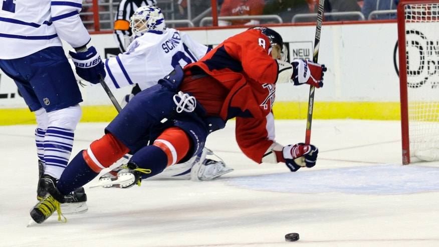 Washington Capitals left wing Alex Ovechkin (8) from Russia, falls to the ice as the puck goes past in the first period of an NHL hockey game against the Toronto Maple Leafs on Tuesday, Feb. 5, 2013, in Washington. (AP Photo/Alex Brandon)