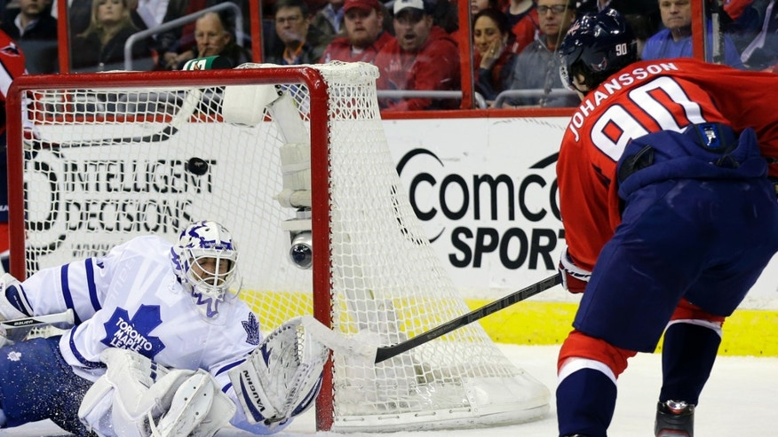 Washington Capitals center Marcus Johansson (90), from Sweden, scores over Toronto Maple Leafs goalie Ben Scrivens in the first period of an NHL hockey game Tuesday, Feb. 5, 2013, in Washington. (AP Photo/Alex Brandon)