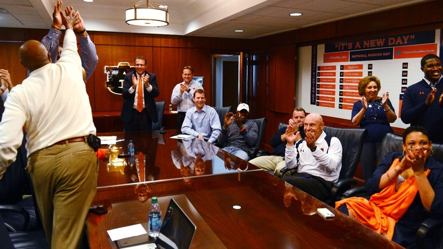 The Auburn coaching stafff reacts to watching Montravius Adams announced that was signing with the Tigers to attend Auburn and play NCAA college football on national signing day on Wednesday, Feb 6, 2013 in Auburn, Ala. Auburn coach Gus Malzahn is standing center.(AP Photo/Todd J. Van Emst)