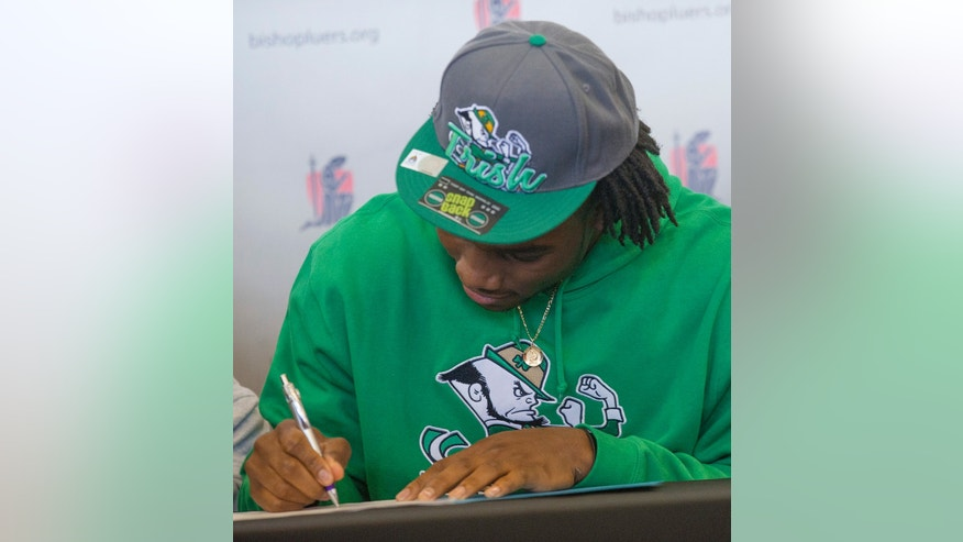 Jaylon Smith, a linebacker from Bishop Luers, signs his letter of intent with Notre Dame, at the high school on Wednesday, Feb. 6, 2013, in Fort Wayne, Ind. (AP Photo/The Journal-Gazette, Swikar Patel) NEWS-SENTINEL OUT  MAGS OUT  NO SALES