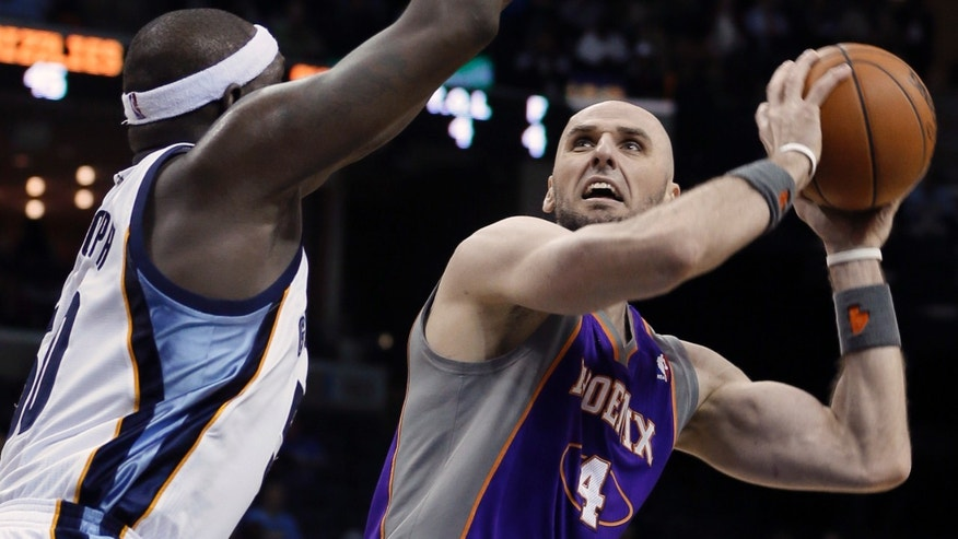 Phoenix Suns' Marcin Gortat (4), of Poland,  tries to shoot around Memphis Grizzlies' Zach Randolph during first half of an NBA basketball game in Memphis, Tenn., Tuesday, Feb. 5, 2013. (AP Photo/Danny Johnston)