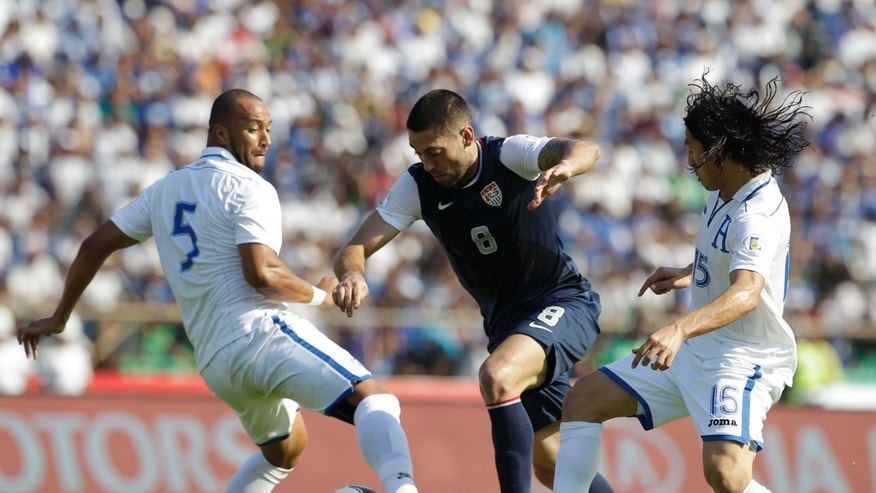 U.S. Clint Dempsey, center, fights for the ball against Honduras' players Victor Bernardez, left, and Roger Espinoza, right, during a 2014 World Cup qualifying soccer game in San Pedro Sula, Honduras, Wednesday Feb. 6, 2013. (AP Photo/Moises Castillo)