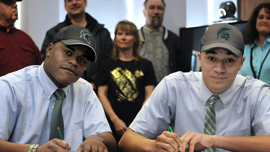 Cathedral Preparatory School seniors Delton Williams, left, and Damion Terry, attend a ceremonial letter-of-intent signing at the school in Erie, Pa., on Wednesday, Feb. 6, 2013. Earlier in the day, they signed their actual letters of intent to attend and play football at Michigan State. (AP Photo/Erie Times-News, Christopher Millette) MAGS OUT, TV OUT