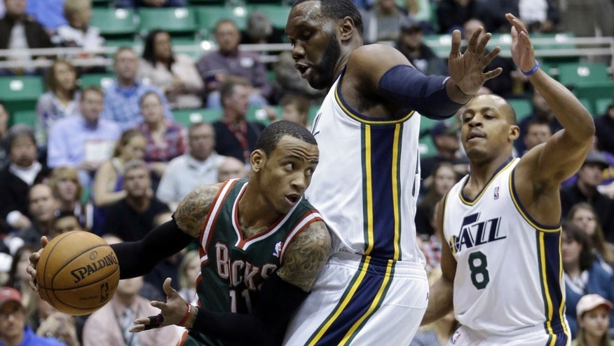Utah Jazz's Al Jefferson, center, and teammate Randy Foye (8) defend against Milwaukee Bucks' Monta Ellis (11) in the first quarter during an NBA basketball game on Wednesday, Feb. 6, 2013, in Salt Lake City. (AP Photo/Rick Bowmer)
