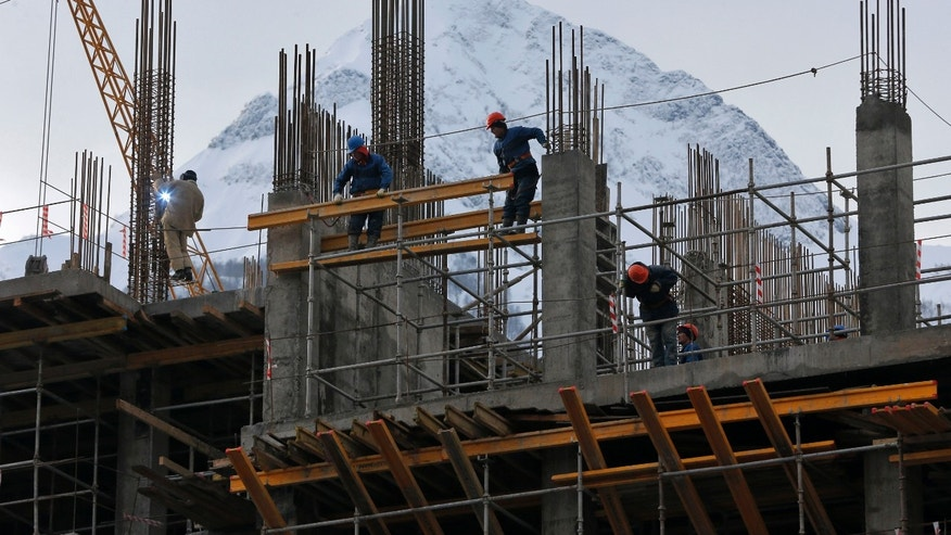In this photo taken on Monday, Feb. 4, 2013, a hotel under construction in Krasnaya Polyana, mountain Olympic cluster, 60 kilometers East from Sochi, Russia. One year from now Russia will be hosting the Winter Olympics at the Black Sea resort of Sochi, and these Games are being built with the hands of thousands migrant workers who are doing all the grunt work that Russians find too low-paid and physically demanding. In a hope to escape their impoverished countries and provide for their families, Central Asian migrants flock to Russia to live in crowded quarters and work long hours.  (AP Photo/Dmitry Lovetsky)