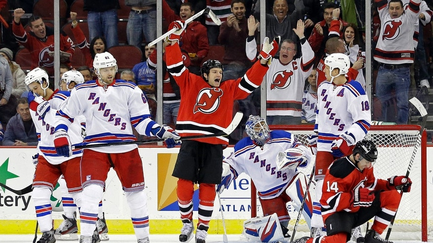 New Jersey Devils' Adam Henrique (14) celebrates with teammate David Clarkson, center right, after scoring a goal against the New York Rangers during the first period of an NHL hockey game, Tuesday, Feb. 5, 2013, in Newark, N.J. (AP Photo/Julio Cortez)