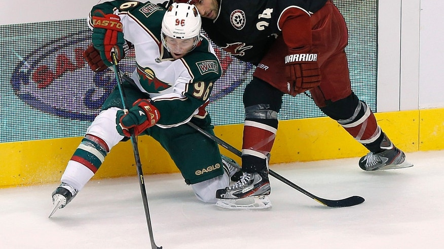 Minnesota Wild's Pierre-Marc Bouchard (96) passes the puck as Phoenix Coyotes' Kyle Chipchura defends during the second period of an NHL hockey game, Monday, Feb. 4, 2013, in Glendale, Ariz. (AP Photo/Matt York)