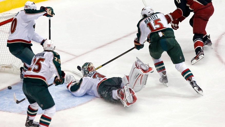 Phoenix Coyotes' Martin Hanzal (17) scores a goal past Minnesota Wild goalie Niklas Backstrom, and Wild's Dany Heatley (15), Jonas Brodin (25) and Ryan Suter (20) during the second period of an NHL hockey game, Monday, Feb. 4, 2013, in Glendale, Ariz. (AP Photo/Matt York)