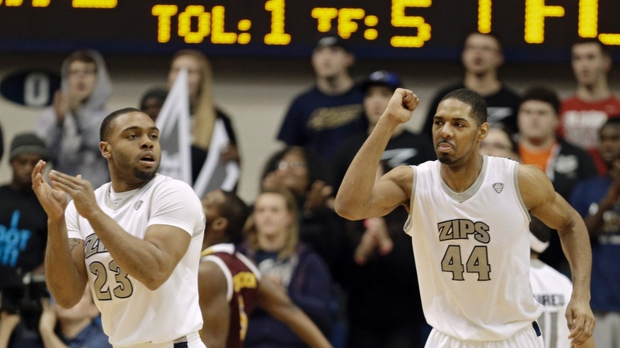 In this photo taken Feb. 5, 2013, Akron's Zeke Marshall (44) celebrates a play with Chauncey Gilliam (23) in an NCAA college basketball game against Central Michigan in Akron, Ohio. With the nation's longest winning streak, a dominant center with NBA potential, a fiery coach and LeBron James as a supporter, Akron could become the next mid-major to make a deep run in the NCAA tournament. (AP Photo/Mark Duncan)