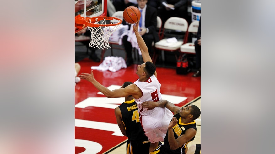Wisconsin's Ryan Evans (5) shoots between Iowa's Roy Devyn Marble and Melsahn Basebe during the first half of an NCAA college basketball game, Wednesday, Feb. 6, 2013, in Madison, Wis. (AP Photo/Andy Manis)
