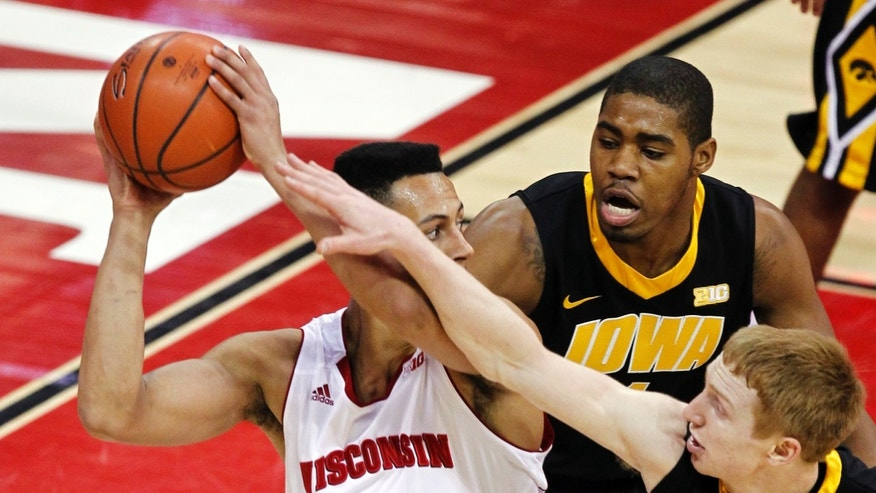 Iowa's Mike Gesell, bottom right, and Melsahn Basabe pressure Wisconsin's Ryan Evans (5) during the first half of an NCAA college basketball game, Wednesday, Feb. 6, 2013, in Madison, Wis. (AP Photo/Andy Manis)