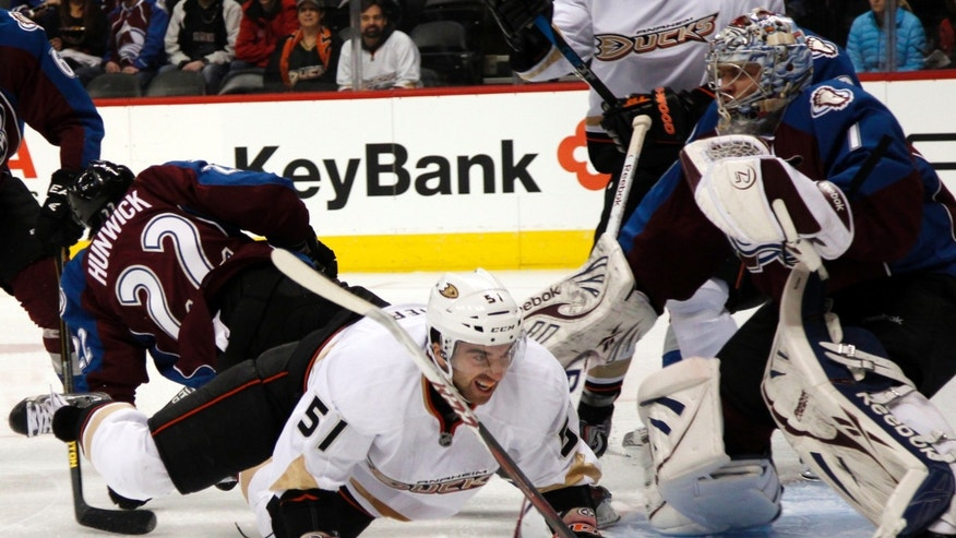 Anaheim Ducks right wing Kyle Palmieri, center, drops to the ice after colliding with Colorado Avalanche defenseman Matt Hunwick, left, as Avalanche goalie Semyon Varlamov, of Russia, protects the net in the first period of an NHL hockey game in Denver, Wednesday, Feb. 6, 2013. (AP Photo/David Zalubowski)