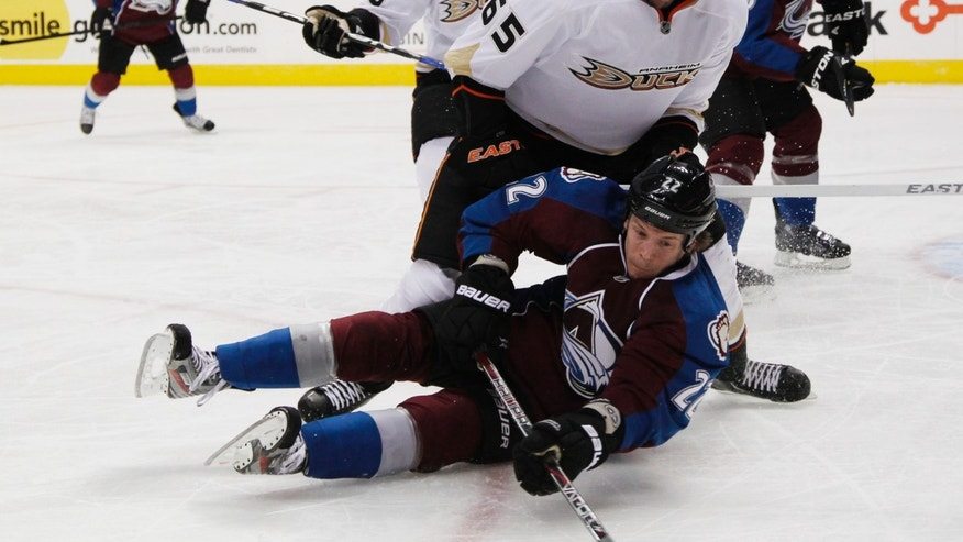 Colorado Avalanche defenseman Matt Hunwick, front, clears the puck after being hit by Anaheim Ducks right wing Emerson Etem, enter, as Ducks right wing Corey Perry looks on in the first period of an NHL hockey game in Denver, Wednesday, Feb. 6, 2013. (AP Photo/David Zalubowski)