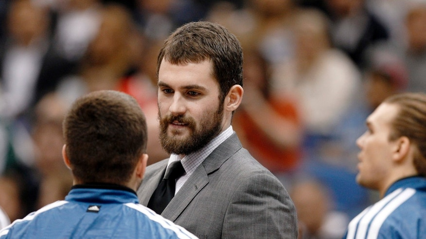 Injured Minnesota Timberwolves forward Kevin Love talks to teammates during a timeout during the first half of an NBA basketball game against the San Antonio Spurs Wednesday, Feb. 6, 2013 in Minneapolis. (AP Photo/Genevieve Ross)