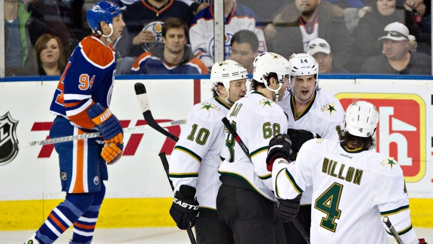 Dallas Stars' Brenden Morrow (10), Jaromir Jagr (68), Jamie Benn (14) and Brenden Dillon (4) celebrate Benn's goal as Edmonton Oilers Ryan Smyth skates past during the second period of an NHL hockey game Wednesday, Feb. 6, 2013, in Edmonton, Alberta. (AP Photo/The Canadian Press, John Franson)