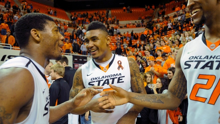 Oklahoma State guard Marcus Smart, left, celebrates with guard Le'Bryan Nash, center, and forward Kamari Murphy, right following an NCAA college basketball game against Baylor in Stillwater, Okla., Wednesday, Feb. 6, 2013. Oklahoma State won 69-67. (AP Photo/Brody Schmidt)