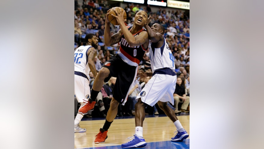 Portland Trail Blazers' Damian Lillard (0) is fouled driving to the basket by Dallas Mavericks' Darren Collison (4) in the first half of an NBA basketball game, Wednesday, Feb. 6, 2013, in Dallas. (AP Photo/Tony Gutierrez)