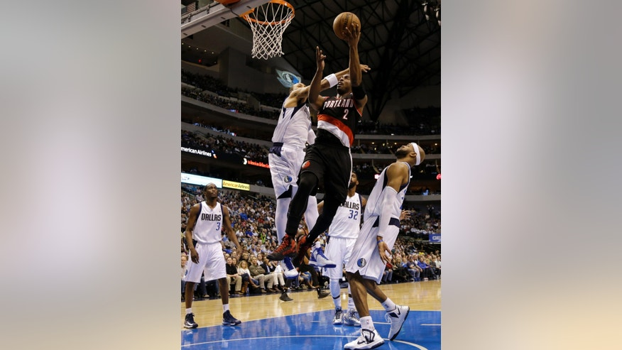 Dallas Mavericks forward Shawn Marion, center left, fouls Portland Trail Blazers guard Wesley Matthews (2) on a shooting attempt in the first half of an NBA basketball game as Mavericks' Rodrigue Beaubois (3) and Vince Carter, right, watch, Wednesday, Feb. 6, 2013, in Dallas. (AP Photo/Tony Gutierrez)