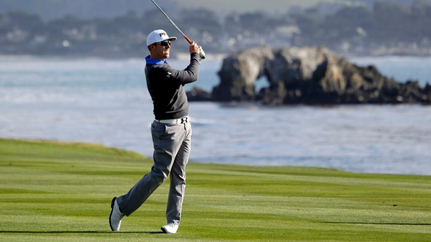 Hunter Mahan hits from the fairway on the 18th hole of the Pebble Beach Golf Links during the first round of the AT&T Pebble Beach Pro-Am golf tournament, Thursday, Feb. 7, 2013, in Pebble Beach, Calif. (AP Photo/Eric Risberg)