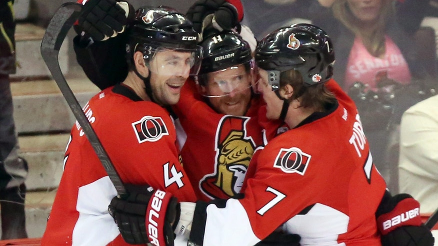 Ottawa Senators' Daniel Alfredsson, center, celebrates his second-period goal against the Carolina Hurricanes with teammates Chris Phillips, left, and Kyle Turris, right, during NHL hockey game action in Ottawa, Thursday, Feb. 7, 2013. (AP Photo/The Canadian Press, Fred Chartrand)