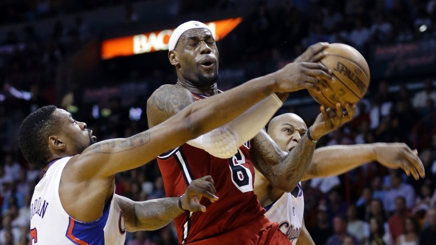 Miami Heat's LeBron James (6) is fouled as he goes to the basket by Los Angeles Clippers' DeAndre Jordan, left, during the first half of an NBA basketball game in Miami, Friday, Feb. 8, 2013. (AP Photo/Alan Diaz)