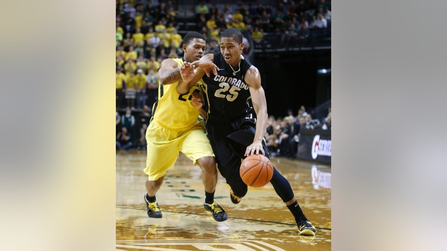 Colorado's Spencer Dinwiddie (25) drives against Oregon's Willie Moore during the first half of an NCAA college basketball game at Matthew Knight Arena in Eugene, Ore. Thursday, Feb. 7, 2013. (AP Photo/Brian Davies)