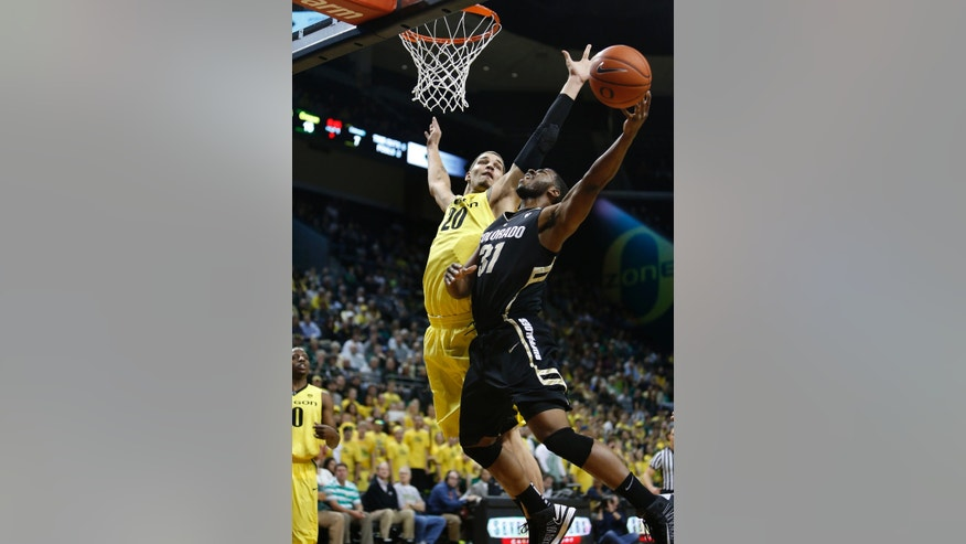 Oregon's Waverly Austin (20) swats away a shot by Colorado's Jeremy Adams (31) during the first half of an NCAA college basketball game at Matthew Knight Arena in Eugene, Ore. Thursday, February 7, 2013. (AP Photo/Brian Davies)