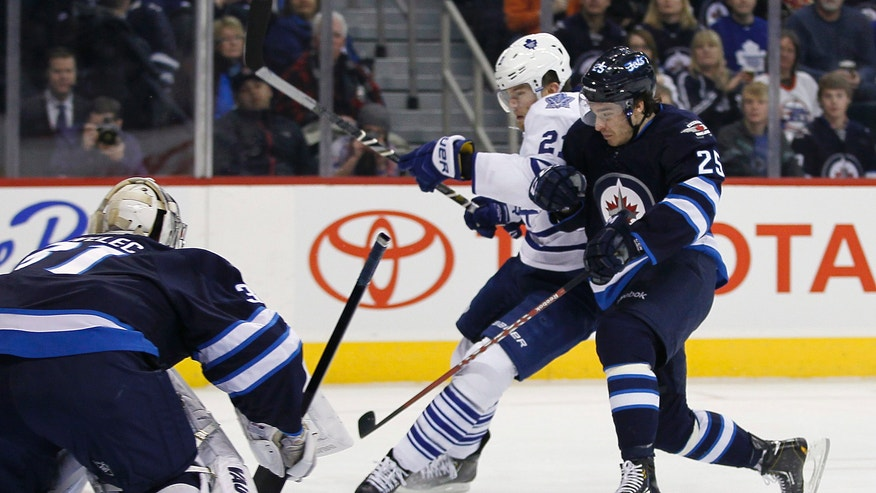 Winnipeg Jets' Zach Redmond (25) takes Toronto Maple Leafs' James van Riemsdyk (21) off the puck in front of goaltender Ondrej Pavelec (31) during second period NHL action in Winnipeg on Thursday, Feb. 7, 2013. (AP Photo/The Canadian Press, John Woods)