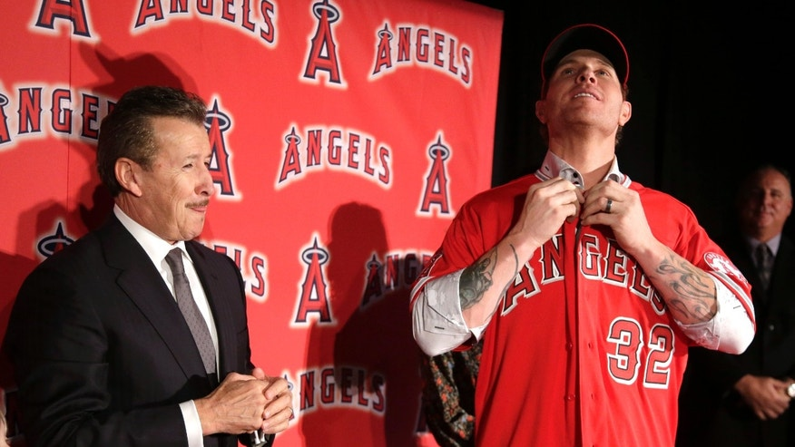 ADVANCE FOR WEEKEND EDITIONS, FEB. 9-10 - FILE - In this Dec. 15, 2012, file photo, Los Angeles Angels owner Arte Moreno, left, watches as free-agent outfielder Josh Hamilton puts on a jersey during a basebalkl news conference in Anaheim, Calif. From Joker Marchant Stadium in Lakeland, Fla., to HoHoKam Park in Mesa, Ariz., bats and balls will be broken out next week when teams start reporting for spring training. (AP Photo/Chris Carlson, File)