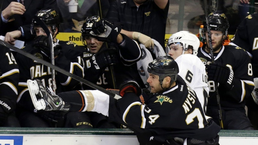 Anaheim Ducks defenseman Ben Lovejoy (6) is knocked into the Dallas Stars bench by Stars left wing Eric Nystrom (24) during the second period of an NHL hockey game on Friday, Feb. 8, 2013, in Dallas. (AP Photo/LM Otero)