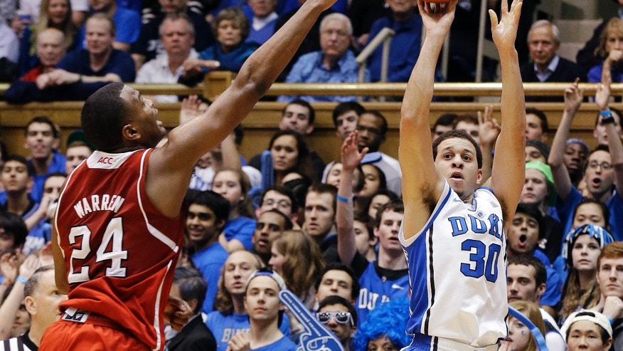 Duke's Seth Curry (30) shoots a 3-pointer as North Carolina State's T.J. Warren (24) defends during the first half of an NCAA college basketball game in Durham, N.C., Thursday, Feb. 7, 2013. (AP Photo/Gerry Broome)