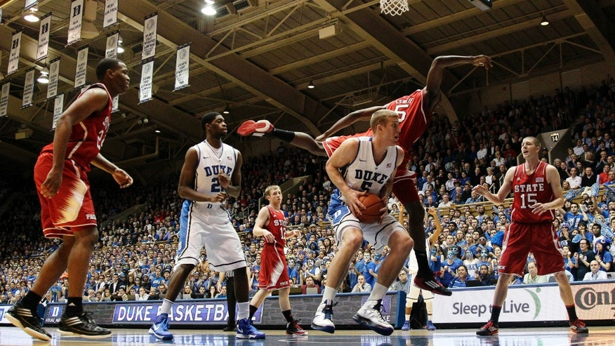 Duke's Mason Plumlee tries to shoot as North Carolina State's C.J. Leslie (5) jumps over during the first half of an NCAA college basketball game in Durham, N.C., Thursday, Feb. 7, 2013. (AP Photo/Gerry Broome)