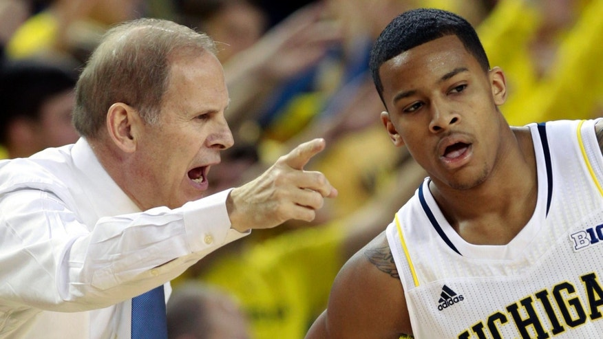 FILE - In this Jan. 6, 2013 file photo, Michigan head coach John Beilein, left, talks with guard Trey Burke (3) during the first half of an NCAA college basketball game against Iowa at Crisler Arena in Ann Arbor, Mich. There are a wide range of title contenders in this college basketball season, including Michigan. (AP Photo/Carlos Osorio, File)