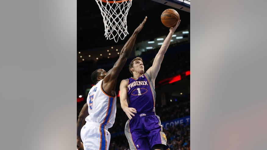 Phoenix Suns guard Goran Dragic (1) shoots in front of Oklahoma City Thunder center Kendrick Perkins (5) during the first quarter of an NBA basketball game in Oklahoma City, Friday, Feb. 8, 2013. (AP Photo/Sue Ogrocki)