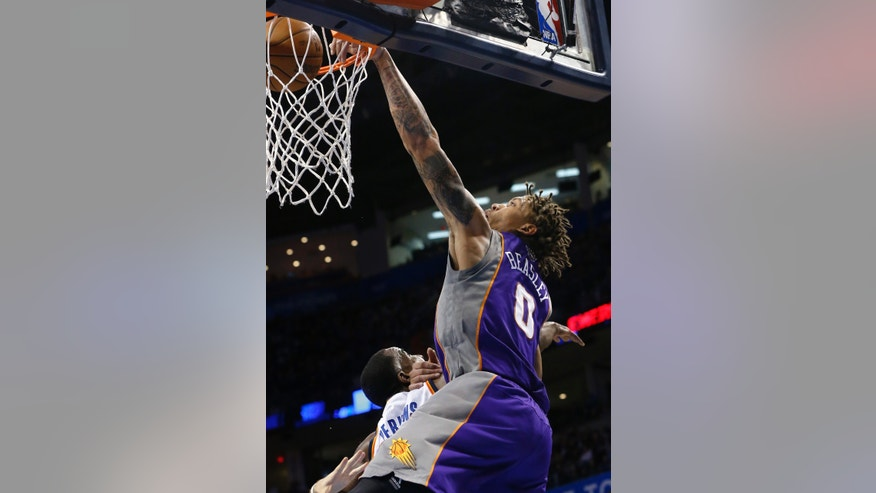 Phoenix Suns forward Michael Beasley (0) dunks in front of Oklahoma City Thunder center Kendrick Perkins during the second quarter of an NBA basketball game in Oklahoma City, Friday, Feb. 8, 2013. (AP Photo/Sue Ogrocki)