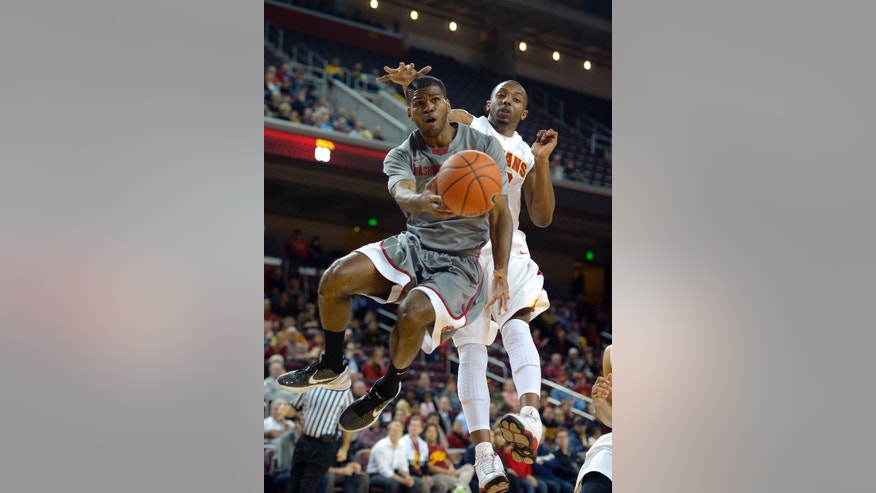 Washington State guard Royce Woolridge, left, passes the ball as Southern California guard Byron Wesley defends during the first half of their NCAA college basketball game, Thursday, Feb. 7, 2013, in Los Angeles. (AP Photo/Mark J. Terrill)